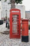 En iconic röd telefonask bredvid en röd stolpeask i St Katharine Docks, London Arkivbild