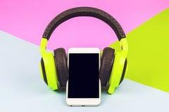en idérik mobiltelefon med hörlurar Arkivbilder
