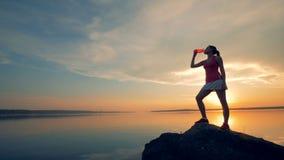 En idrottskvinna dricker vatten nära en sjö En flicka dricker från en special flaska på en solnedgångbakgrund nära sjön stock video