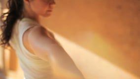 En idrottskvinna som gör asanas som blir på matting i yogastudiocloseup arkivfilmer