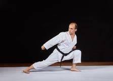 En idrottsman nen gör ett kvarter med hans hand i en låg karatekugge Royaltyfri Foto