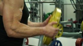 En idrottsman nen lyfter en diskett, en övning för händer stock video