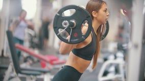En idrottsman nenkvinnautbildning i idrottshallen - squatting med hanteln den på skuldrorna lager videofilmer