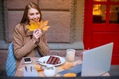 En iklädd flicka ett lag som sitter i ett kafé, med en bärbar dator, ler och rymmer en höstlövverk utanför Royaltyfria Foton