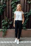 En iklädd härlig flicka en vit t-skjorta står utomhus, agaen arkivfoto
