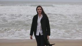 En iklädd höst för härlig flicka beklär att gå på stranden från havet in mot kameran stock video