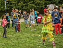 En iklädd kvinna en clowndräkt spelar med barn i fren Royaltyfria Bilder