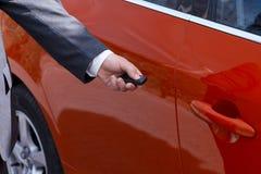 En iklädd man en grå dräkt öppnar eller stänger hans bil arkivbild