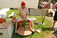 En iklädd medeltida dräkt för keramiker gör en vas Arkivfoto