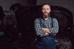 En iklädd skäggig sakkunnig mekaniker en likformig som står med korsade armar mot en bil i garaget fotografering för bildbyråer