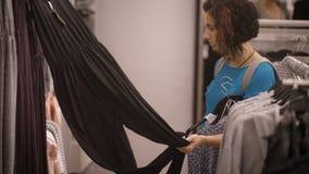 En iklädd ung flicka en blå T-tröja och grå färg vandrar på baksidan för att välja mellan violett och svart jumpsuiten för den gr stock video
