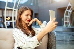 En iklädd ung härlig flicka en randig trendig klänning sitter i ett utomhus- kafé för sommar och väntar på hennes beställning och arkivfoton