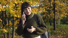 En iklädd ung kvinna en grön tröja använder en smartphone i hösten parkerar arkivfilmer