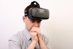 En illamående, yr störd man som bär hörlurar med mikrofon för virtuell verklighet för Oculus klyfta VR efter en negativ erfarenhe Arkivfoto