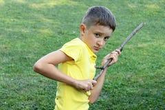 En ilsken framsida för pojkewitn som rymmer en pinne i hans händer arkivfoton