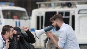 En ilsken man med ett skägg ropar högt på folk i en megafon stock video