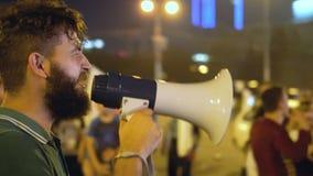 En ilsken man på samlar agiterar megafonen med folkmassan och ger starkt anförande stock video