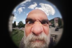 En ilsken man som ser till en kikhåldörr Arkivbilder