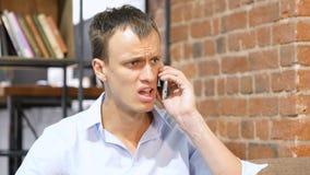 En ilsken och rasande bussinessman ropar till telefonen Arkivfoto