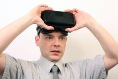 En imponerad, lättad paff man som bär hörlurar med mikrofon för virtuell verklighet för Oculus klyfta VR Arkivfoton