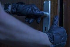 En inbrottstjuv öppnar försiktigt en plan dörr med hans händer royaltyfri fotografi