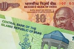 En indier 10 rupie anmärkning med en iranier 10000 Rial sedel arkivfoton