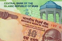 En indier 10 rupie anmärkning med en iranier 10000 Rial sedel royaltyfri fotografi