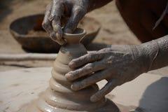 En indisk keramiker gör jord- lampor eller 'diyas' framåt av den kommande Diwali festivalen Arkivfoto