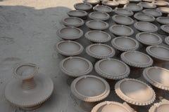 En indisk keramiker gör jord- lampor eller 'diyas' framåt av den kommande Diwali festivalen Arkivfoton