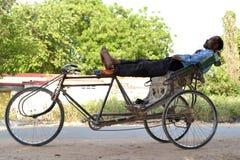 En indisk rickshawpuller som vilar i konstig position Arkivfoton