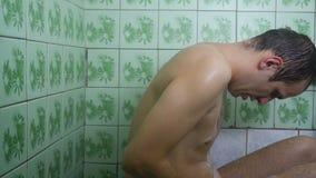En influten man det fruktansvärda duschrummet för dusch stock video