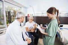 En informes de mirada pacientes mayores del doctor While Nurse Holding fotografía de archivo
