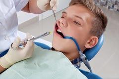 En injektion av anestesi till patienten Arkivfoto