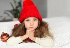 En inomhus stående av lite flickan i stuckit hållande julpynt för ett varmt rött lock - ett foto som föreställer ett begrepp fotografering för bildbyråer