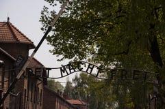 En inskrift ovanför maingaten till koncentrationsläger i Ausc arkivbild