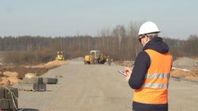 En inspektör i en signalväst och en vit hjälm med svarta exponeringsglas gör anmärkningar i hans mapp på kvaliteten av vägen stock video