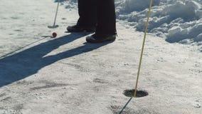 En invierno, al jugar a golf, un hombre sostiene un palillo y tiene como objetivo la bola almacen de video