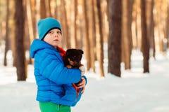 En invierno el día frío calienta el perrito del muchacho Fotos de archivo