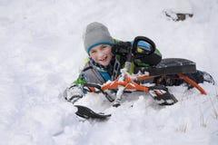 En invierno, el muchacho nevado del bosque se cayó de un trineo Foto de archivo
