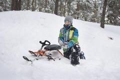En invierno, el muchacho nevado del bosque se cayó de un trineo Imágenes de archivo libres de regalías