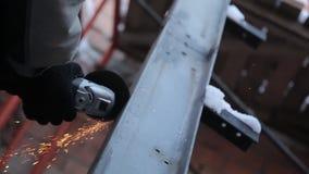 En invierno el trabajador corta el perfil con un cortador del metal almacen de metraje de vídeo