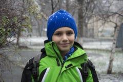 En invierno, la calle es un muchacho debajo de nieve que cae Foto de archivo libre de regalías