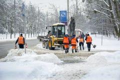 En invierno, en nevada, los trabajadores y un tractor limpian el camino franco Fotografía de archivo