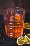 En iskub svävar i alkohol i ett exponeringsglas Arkivbild