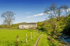 En isolerad ladugårduppsättning i grön engelsk countyside av en bana som tillsammans med kör en flod Fotografering för Bildbyråer
