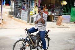 En ivoriansk man meddelar med hans mobiltelefon arkivbild
