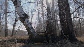 En jägare med ett vapen går till och med skogen och stoppen att vila på en trädstam stock video