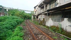 En järnväg omger husen arkivfoton
