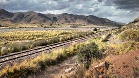 En järnvägsspår som leder till och med det torra landskapet av sydliga Peru Arkivbild