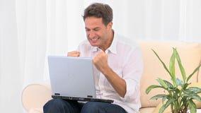 En jätteglad man med hans bärbar dator arkivfilmer